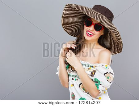 Cheerful beautiful girl in hat and heart-shaped sunglasses. Smiling widely, looking at camera, touching hair. Summer outfit. Waist up, studio, indoors