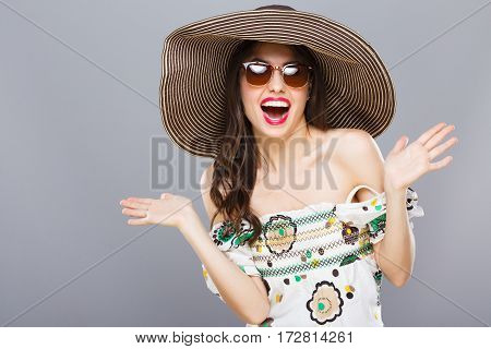 Cheerful beautiful girl in hat and sunglasses. Smiling widely, surprised, looking at camera, hands aside. Summer outfit. Waist up, studio, indoors