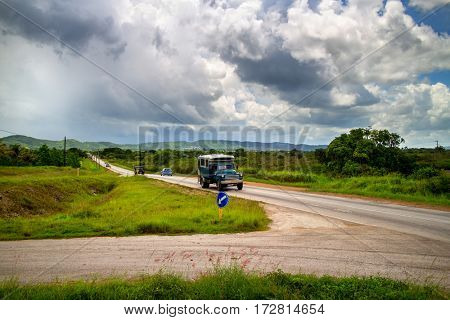 SANTA CLARA, CUBA - July 16, 2013: Vintage American car on a highway close to Santa Clara city in Cuba, in background is typical Cuban landscape.