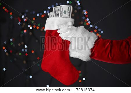 Santa Claus hand holding Christmas stocking with money on blurred lights background