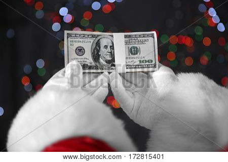 Santa Claus hands holding money on blurred lights background