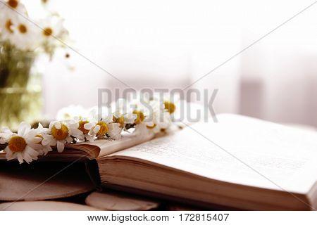 Beautiful chamomile wreath on book