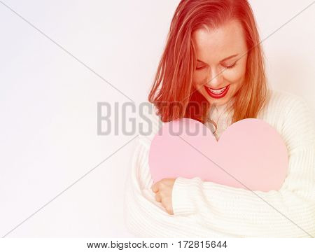 A caucasian woman is smiling holding heart.