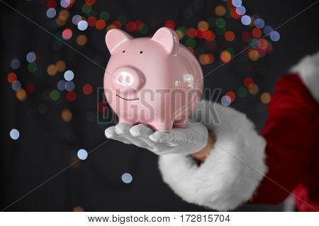 Santa Claus hand holding piggy bank on blurred lights background