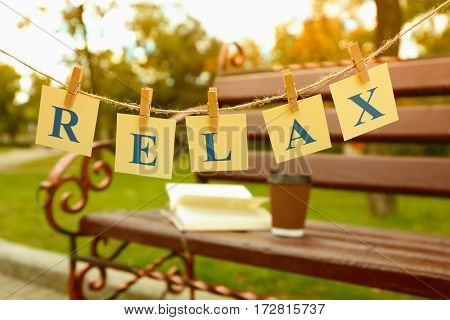 Cards with printed word RELAX on park bench background