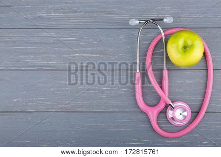 Stethoscope with apple on wooden table