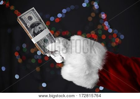 Santa Claus hand holding money on blurred lights background