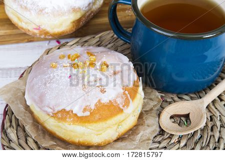 Tasty donuts with icing on baking paper