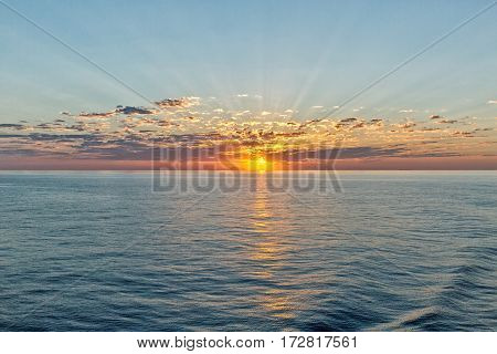 beautiful seascape with deep ocean waters and sunrise cloudscape looking back towards one of the many Greek Islands
