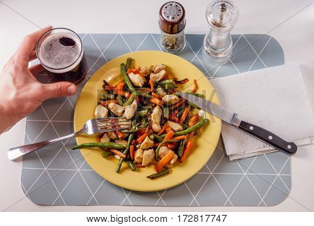 vegetables with meat on yellow plate male hand