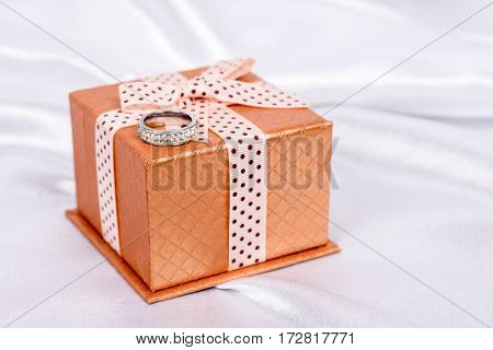 Brown Gift Box With Bow And Diamond Ring Over White Satin