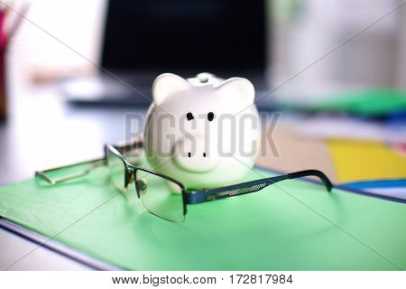 Office workplace with money box and glasses on wood table.