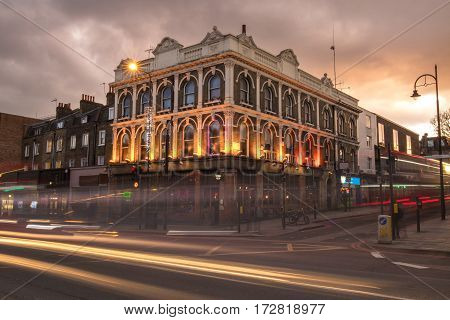 Victorian building in a road corner at a cold brownish twilight in london. Long exposure showing the headlamps of cars and bus as lines of light