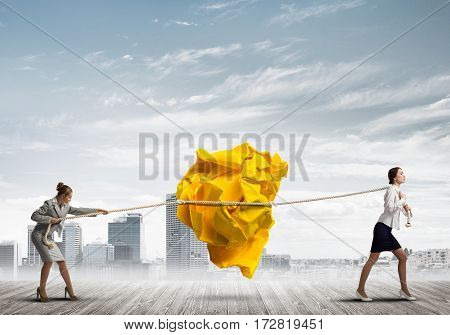 Two businesswomen outdoors playing tug of war game