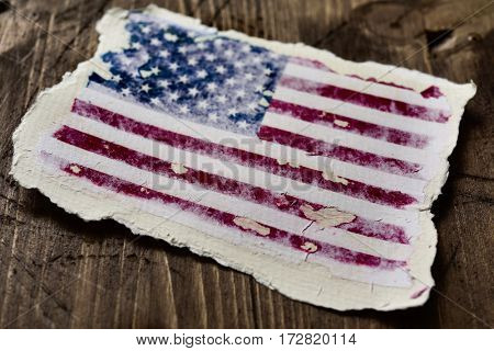 the flag of the United States in an aged piece of paper on a rustic wooden background