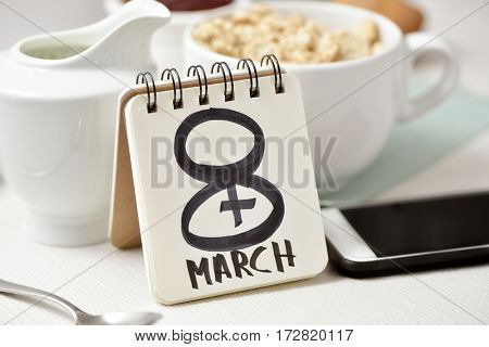 the text 8 March, observance of the womens day, handwritten in the page of a notebook placed on a table set for breakfast, with a bowl with cereals and a smartphone in the background