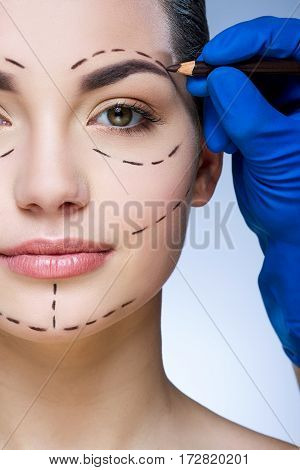 Close up portrait girl with dark eyebrows at studio background, doctor's hand making marks on patient's face, portrait, perforation lines on face, close up.
