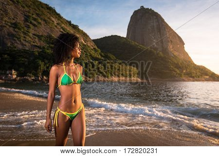 Young Beautiful Brazilian Woman in Bikini Walking at the Beach by Sunrise With the Sugarloaf Mountain in the Background, in Rio de Janeiro