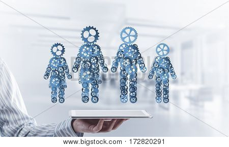 Close of businessman holding tablet pc with figures of family made out of gears. Mixed media