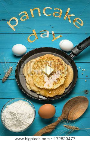 Hot delicious pancakes in frying pan on blue wooden table with flour and eggs. Pancake day background