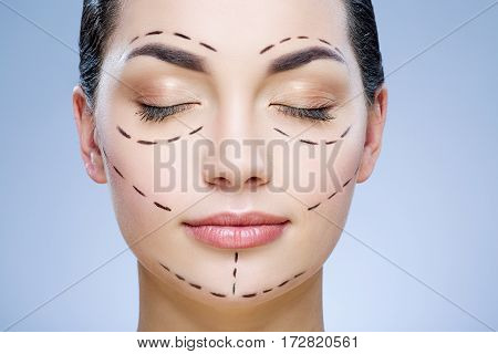 Young girl with dark hair at gray studio background, perforation lines on face, portrait, closed eyes.