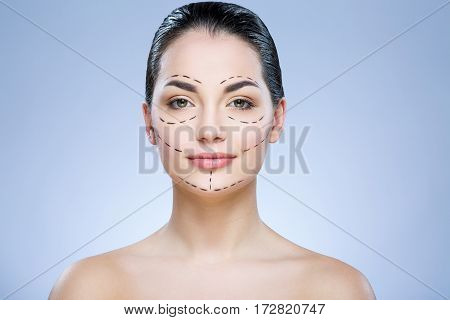 Beautiful girl with dark hair looking at camera at gray studio background, perforation lines on face, portrait.
