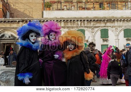 Venice, Italy - February 19 2017: Carnival mask and costume poses. Masked persons in traditional costume pose at a Venetian square during the Venice 2017 Carnival.