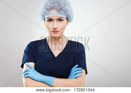 Lovely nurse with nude make up wearing blue medical uniform, medical hat at gray background, copy space.