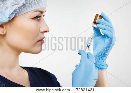 Portrait of  nurse with nude make up wearing blue medical uniform, medical hat and gloves at gray background, holding syringe, close up.