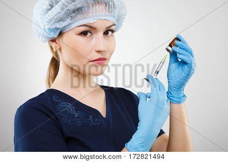 Lovely nurse with nude make up wearing blue medical uniform, medical hat and gloves at gray background, holding syringe.