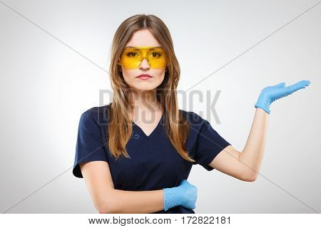 Cute nurse with brown hair and nude make up wearing blue medical uniform, yellow glasses and gloves at gray background and looking at camera, copy space.
