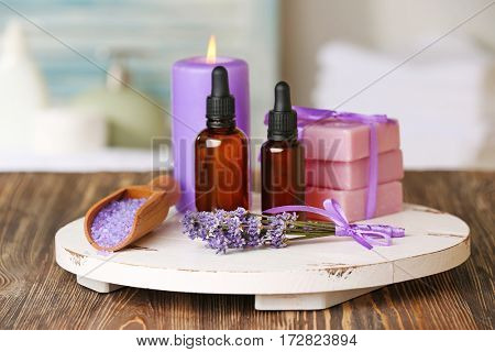 Bottles of essential oil with lavender, sea salt, soap and candle on wooden board