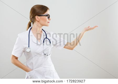 Nice nurse with brown hair and nude make up wearing white medical robe, stethoscopes and glasses at gray background, copy space, pointing right.