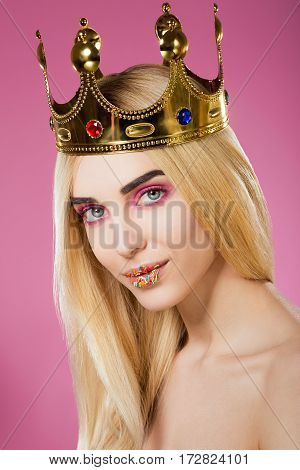 Gorgeous young girl with big eyes, dark eyebrows, sweet lips and naked shoulders wearing crown and looking at camera at pink background, portrait.