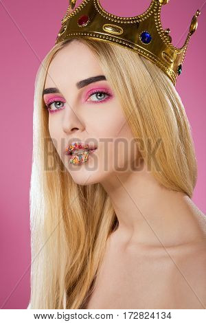 Cute young girl with big eyes, dark eyebrows, sweet lips and naked shoulders wearing crown and looking at camera at pink background, portrait, make up model.