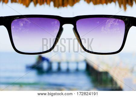 Black sunglasses at sea and beach umbrella background, copy space, close up.