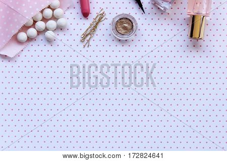 Gumballs and beauty products frame open polka dot space for copy.