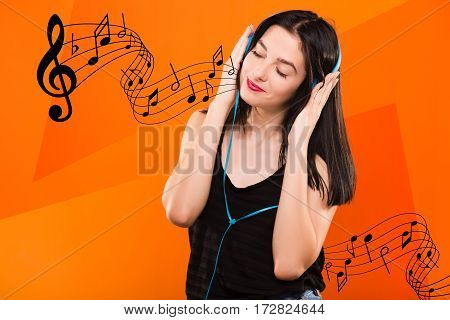 Young beautiful brunette girl, in black blouse, listening to music with big blue headphones on geometric orange background with musical notes