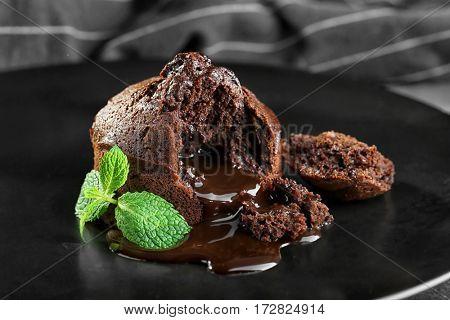 Chocolate fondant with mint on plate, closeup