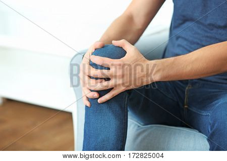 Young man suffering from pain in knee at home, closeup