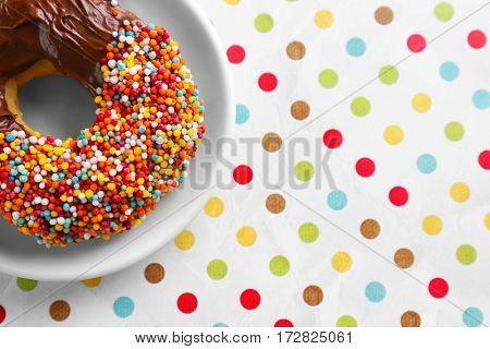 Plate with tasty glazed donut on colorful background