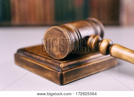 Judge gavel with sound block and books on background