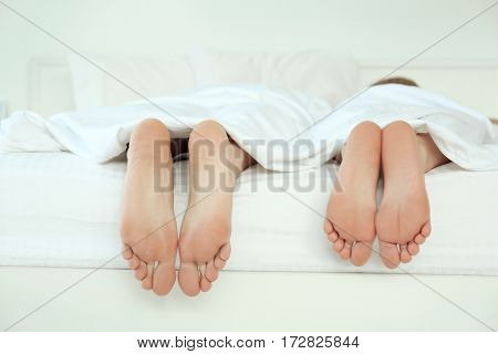 Couple's feet in bed, closeup