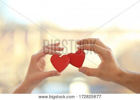 Male and female hands holding small red hearts on blurred background