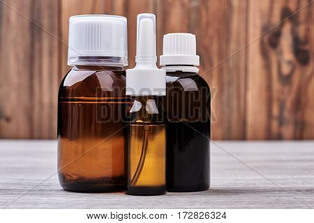 Remedy vials on wooden background. Medicines on a shelf. Quick way to get well.