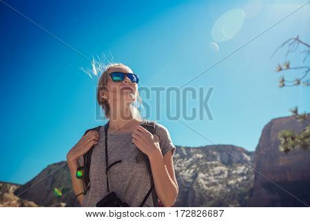 Tourist with camera standing in the mountains