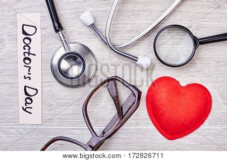 Stethoscope, glasses and magnifying glass. Greeting card for a doctor.