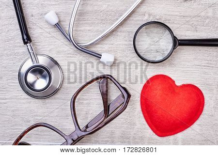 Red heart, loupe and stethoscope. Spectacles on wooden backdrop. Consult your doctor.
