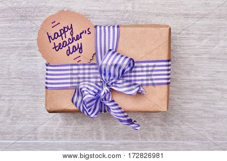 Present box for Teacher's Day. Striped bow on a gift. Warm greetings for teacher.