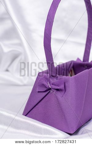 Purple Flower Arrangement Box With Bow On The White Satin